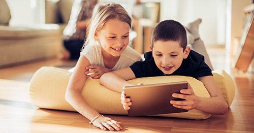 Children using tablet device on living room floor