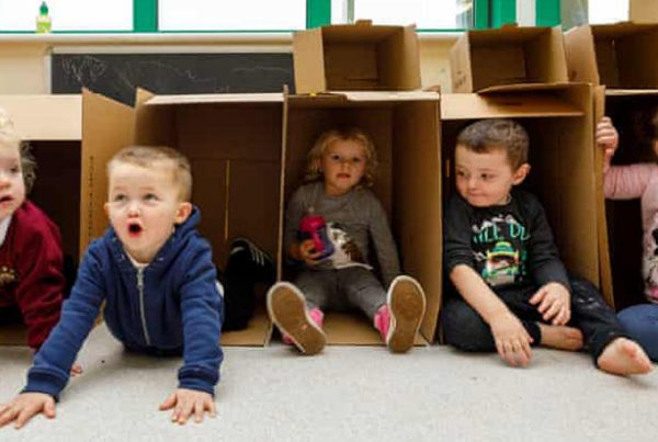 Nursery children playing with boxes