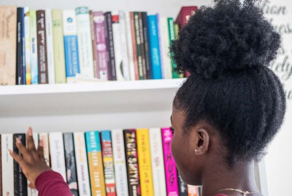 Girl choosing book from bookcase