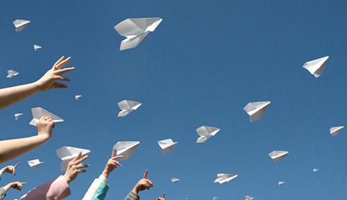 Hands throwing paper aeroplanes