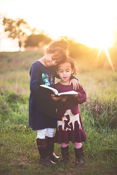 Children reading in field together