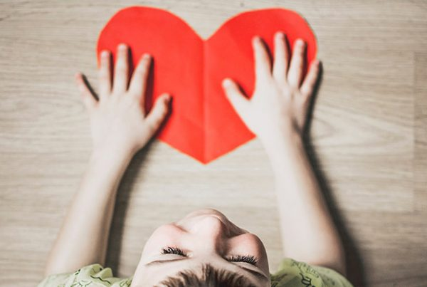Child with red paper heart