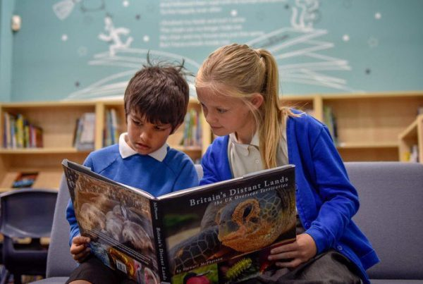 Two children reading book in school library
